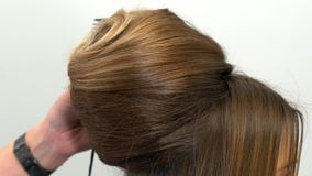 Профессиональный парикмахер демонстрирует законченный стиль причесок и завершает поправки акции видеоматериалы