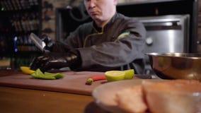 Профессиональный повар прерывая с зеленым цветом острого ножа и желтыми болгарским перцем и известкой на деревянной доске для под акции видеоматериалы