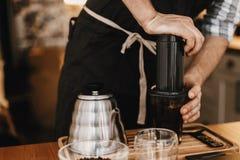 Профессиональное barista подготавливая кофе в aeropress, альтернативный метод заваривать кофе Руки на aeropress и стеклянной чашк стоковые фото
