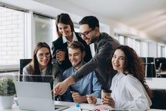 Профессионалы дела Группа в составе молодые уверенно бизнесмены анализируя данные используя компьютер пока тратящ время в офисе стоковое изображение