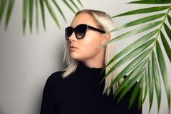 Профиль красивой женщины с солнечными очками пряча за тропическими листьями ладони стоковые фото