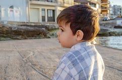 Профиль 2 лет старого малыша на море doc на золотом часе стоковое изображение