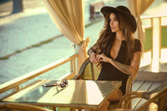 Пlam tattooed brunette in little black dress and trendy wide brimmed fedora hat sitting in the nice summer restaurant. Portrait of glam tattooed brunette in royalty free stock image