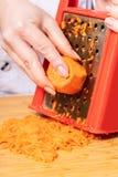 Повар трет морковей на терке стоковая фотография