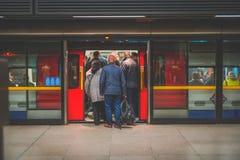 Поезд людей всходя на борт в час пик на канереечном причале, станции стоковое фото