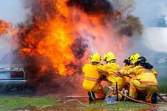Пожарный используя автомобиль воды и гасителя горящий, пожарные используя гаситель и воду от шланга для противопожарного, горящег стоковая фотография