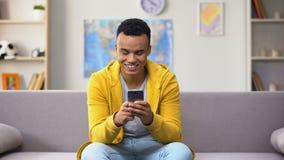 Позабавленный Афро-американский молодой мужской перечисляя смартфон, получая действительное предложение сток-видео