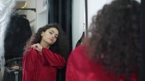 Покупатель женщина одела красную мантию моды наслаждается ее отражением в зеркале сток-видео