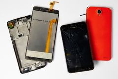 Broken mobile phone. Disassembled mobile phones on a white background royalty free stock images