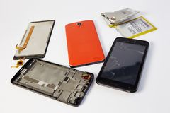 Broken mobile phone. Disassembled mobile phones on a white background stock photos