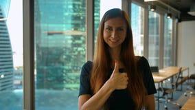 Получите как Оптимистическая коммерсантка делает большой палец руки жестов рукой вверх по знаку в офисе акции видеоматериалы