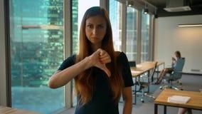 Получите нелюбовь Большие пальцы руки вниз красивым женским усаживанием крытым сток-видео