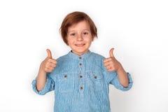 Положение студии мальчика изолированное на серых больших пальцах руки вверх по смотреть ослабленную камеру стоковое фото