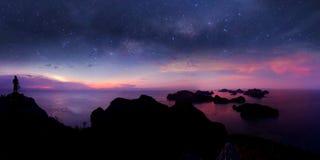 Положение человека на горе с взглядом панорамы и миллионом галактиками звезд стоковые фотографии rf
