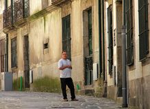 Положение человека около двери на некоторой узкой улочке Порту стоковая фотография