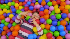 Положительная концепция эмоций Предпосылка школьных каникулов Игры Preschooler с шариками Мальчик в бассейне с мягкими шариками ш акции видеоматериалы
