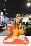 Положительная девушка держа стекло с напитком в руке, есть французский картофель фри, взгляды на камере и усмехаться стоковое фото