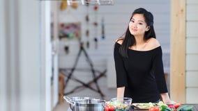 Положительная очаровательная молодая азиатская сексуальная женщина представляя и смотря камеру во время варить видеоматериал
