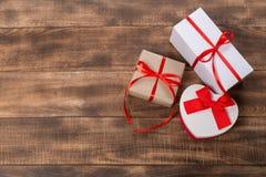 Подарки с красной лентой на деревянном столе стоковое фото