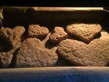 Подготавливает печенья в печи, печет печенья в форме сердца стоковая фотография