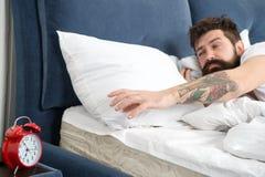 Подсказки для просыпать вверх предыдущее Кровать стороны бородатого хипстера человека сонная с будильником Поверните это звеня Чт стоковое фото rf