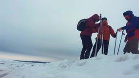Подъем товарища по команде порции альпиниста, человек с рюкзаком достиг вне руку помощи к его другу 3 альпиниста на a акции видеоматериалы