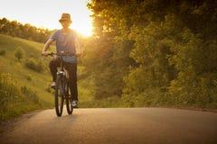 Подросток ехать велосипед на лете дороги sunlit стоковые фото