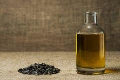 Подсолнечное масло в стеклянной бутылке, и пригорошня семян подсолнуха на предпосылке мешковины стоковые изображения rf