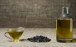 Подсолнечное масло в стеклянной шлюпке подливки, в бутылке, и пригорошня семян подсолнуха на предпосылке мешковины стоковое фото rf
