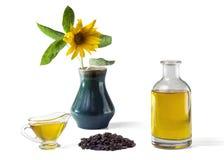 Подсолнечное масло в стеклянной шлюпке подливки и в бутылке, пуке семян подсолнуха и солнцецвете в вазе стоковое фото rf