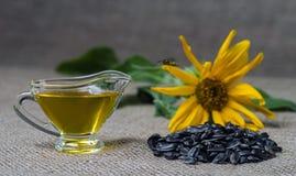 Подсолнечное масло в стеклянной шлюпке подливки и пригорошня семян подсолнуха на предпосылке мешковины и солнцецвета Оса летания стоковое фото rf