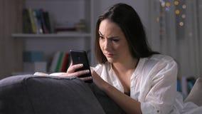 Подозрительная женщина проверяя содержание телефона в ночи акции видеоматериалы