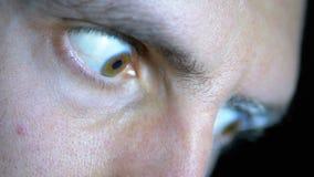 Посмотрите страха, глазы навыкате молодого человека на черной предпосылке сток-видео