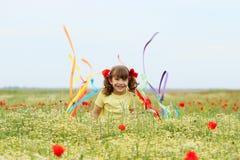 Потеха маленькой девочки и развевать с красочными лентами на весеннем сезоне луга стоковое фото