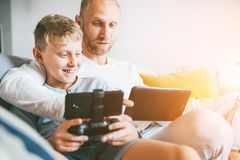 Потехи игроков игры отца и сына сидят совместно используя планшет и gamepad дома на уютной софе стоковые изображения