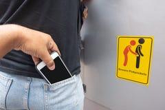 Похититель крадя мобильный телефон из заднего кармана женщины с остерегает карманников подписывает предпосылку символа стоковое фото rf