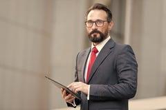 Портрет бизнесмена с таблеткой в руке на предпосылке офисного здания Бизнесмен используя его таблетку из офиса с 4G стоковое фото