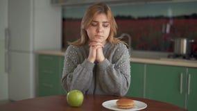Портрет внимательной пухлой женщины друг смотря бургер и зеленое яблоко в кухне выбор трудный сток-видео