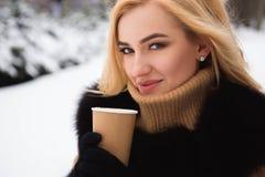 Портрет европейского кофе модной женщины стиля выпивая в парке зимы стоковое изображение