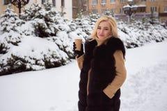 Портрет европейского кофе модной женщины стиля выпивая в парке зимы стоковая фотография