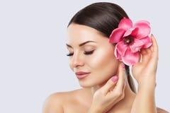 Портрет женщины с красивым макияжем держит цветок магнолии в его руках стоковое фото