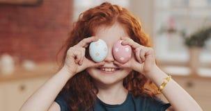 Портрет жизнерадостной девушки маленького ребенка redhead играя с пасхальным яйцом на предпосылке кухни Она веселит и стоковое фото