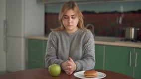 Портрет жирной девушки делая выбор между здоровой и нездоровой едой сидя на таблице в кухне Сало акции видеоматериалы