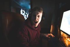 Портрет злого gamer сидя на компьютере в уютной комнате, сердитый и смотря в камеру стоковое изображение