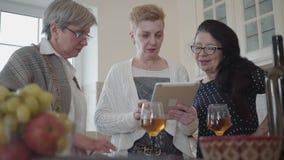 Портрет 3 зрелых девушек наблюдая что-то интересное на планшете и активно обсуждает adulteration акции видеоматериалы