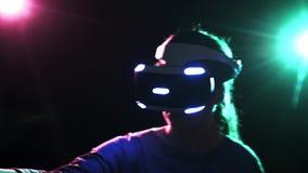 Портрет играя женщину в шлемофоне VR на темной предпосылке сток-видео