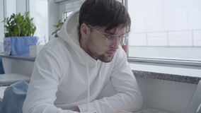 Портрет красивого парня сидя в кафе, ждать его заказ или в эпицентре деятельности и работая умышленно на компьютере сток-видео