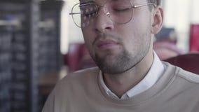 Портрет красивого человека кладя часть еды в его конец рта вверх Клиент удовлетворяется с его обедающим, он закрывает видеоматериал