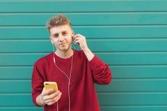 Портрет красивого человека слушая музыку в наушниках и смотря камеру стоковые изображения