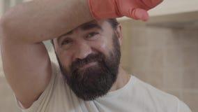 Портрет красивого человека с идеальной бородой усмехаясь после работы и убирать полностью его нового современного дома сток-видео